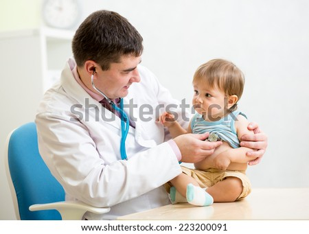 doctor man examining heartbeat of child boy with stethoscope - stock photo