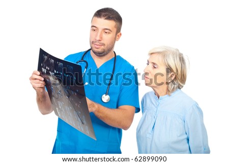 Doctor man showing and explaining his patient senior woman  the MRI scans results - stock photo