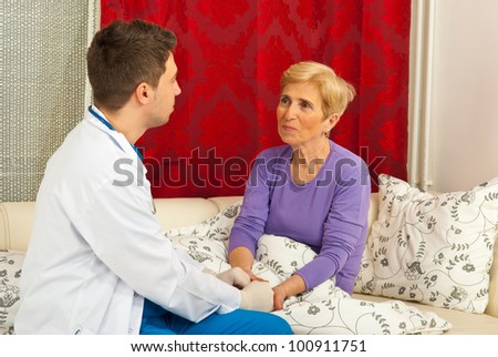 Doctor man talking with patient senior woman in her home