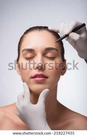 Doctor marking face of woman before the plastic surgery - stock photo