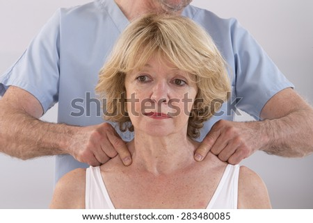 Doctor massaging his patient neck in medical office - stock photo