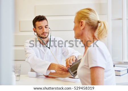 Doctor measures blood pressure from patient during examination