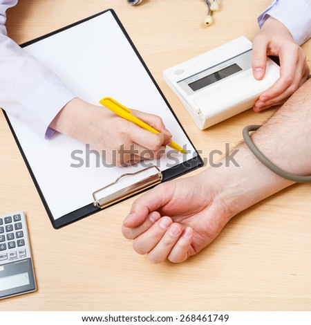 doctor measures blood pressure of patient during appointment - stock photo