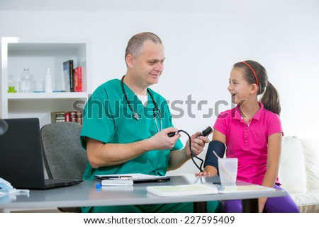 Doctor measures the pressure of a little girl