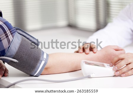 Doctor measuring blood pressure of a woman - stock photo