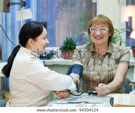 Doctor measuring blood pressure of patient  in clinic - stock photo
