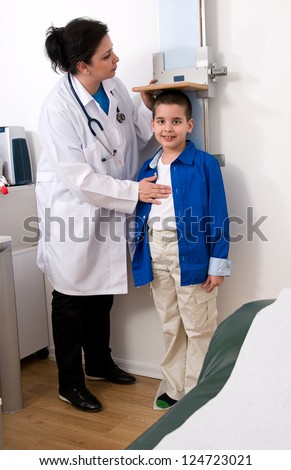 Doctor measuring little child boy height growth at clinic. - stock photo