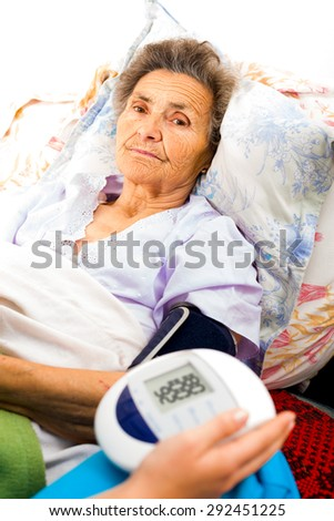 Doctor measuring senior patients blood pressure. - stock photo