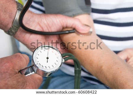 doctor measuring the blood pressure at a senior patient - stock photo