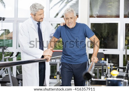 Doctor Motivating Senior Man To Walk In Fitness Studio - stock photo