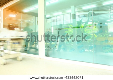 Doctor,moving patient through hospital corridor