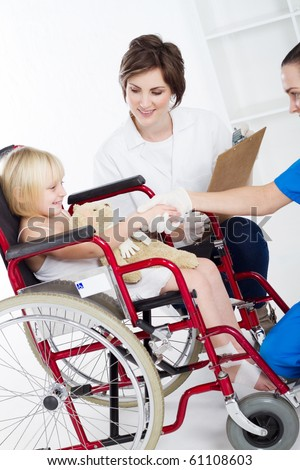 doctor, nurse shake hands with little girl patient - stock photo