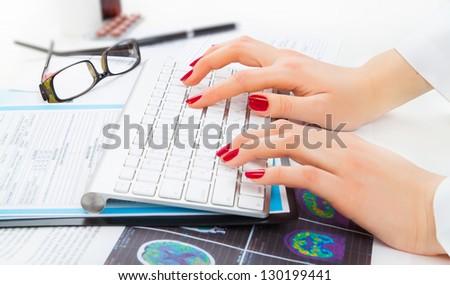 Doctor, nurse writing on keyboard - stock photo