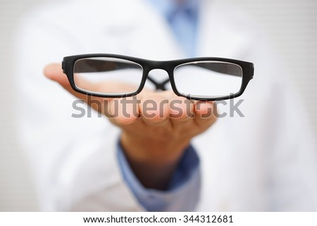 doctor oculist   offering  a pair of eyeglasses. concept of good vision - stock photo