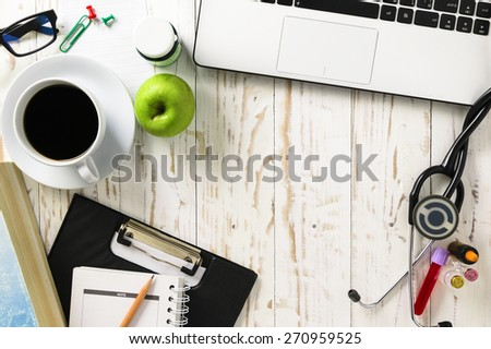 Doctor office,Top view ,Laptop (notebook) with cup of coffee and notepad,book with pen and  stethoscope with medicine on wood table.(Copy space on center) - stock photo