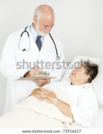 Doctor on his rounds, talking to a patient in the hospital. - stock photo