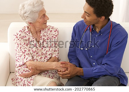 Doctor or care giver holding elderly lady's hands.  - stock photo