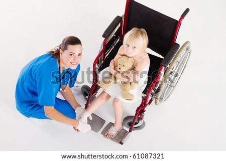 doctor or nurse bandage little patient's ankle - stock photo