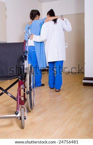 doctor or nurse helping her patient to walk without wheelchair - stock photo