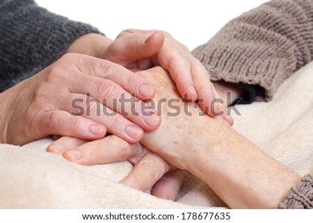 Doctor or nurse holding elderly wrinkled hand - stock photo