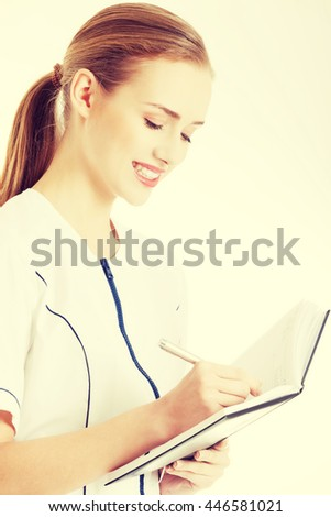 Doctor or nurse is writing in notebook. - stock photo