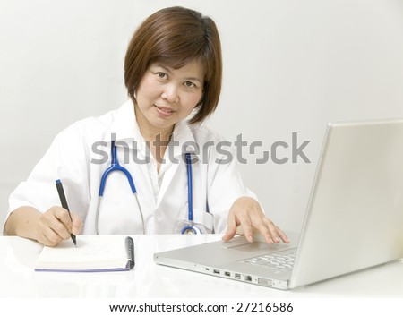 Doctor or Nurse sitting sitting at her desk and writing