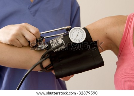 Doctor or nurse taking a patient's blood pressure - stock photo