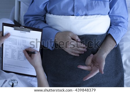 Doctor or nurse talking to patient and reviewing his medical history  - stock photo