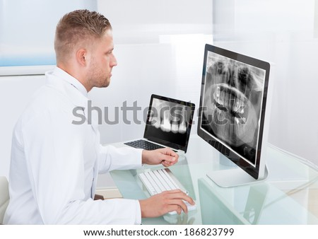 Doctor or radiologist looking at an x-ray online displayed on a desktop monitor as he makes a diagnosis or checks prognosis - stock photo
