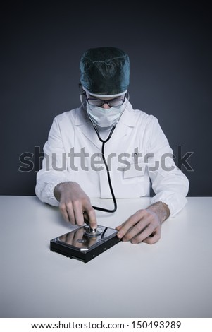 Doctor or Technician wearing a lab coat and stethoscope examining an hard disk - stock photo