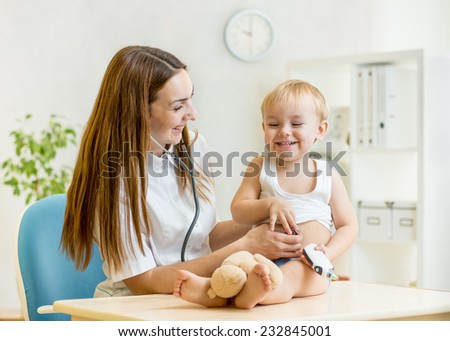 doctor pediatrician examining of kid boy with stethoscope - stock photo