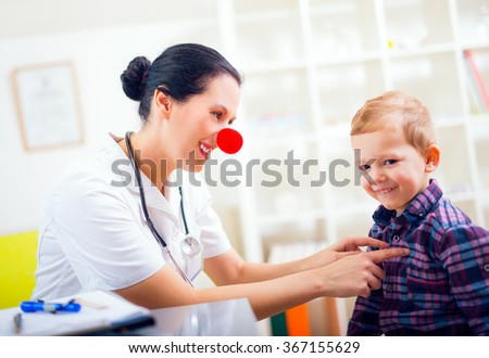 Doctor pediatrician with clown nose and  happy child patient  - stock photo