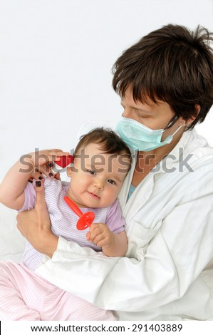 Doctor pediatrician with protective mask examining baby girl