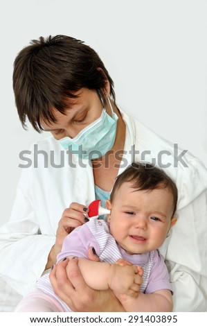 Doctor pediatrician with protective mask examining baby girl - stock photo