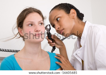Doctor peering into her patients ear with an instrument - stock photo