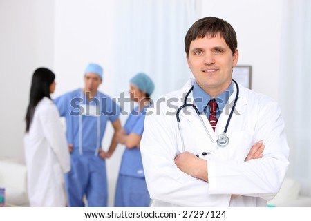 Doctor portrait with medical personnel in background