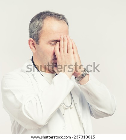 Doctor praying for help. Young man medical doctor surgeon or nurse portrait. - stock photo