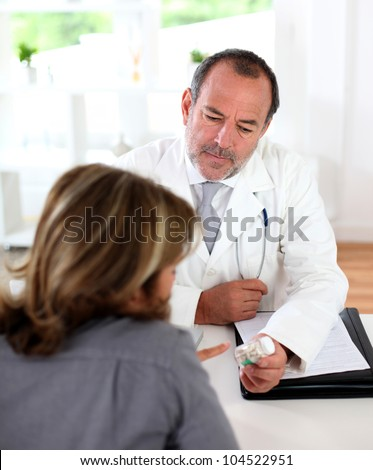 Doctor prescribing medication to patient - stock photo