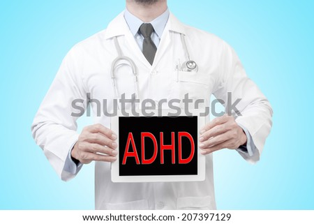doctor presenting diagnosis ADHD word in digital tablet screen concept for medical  - stock photo