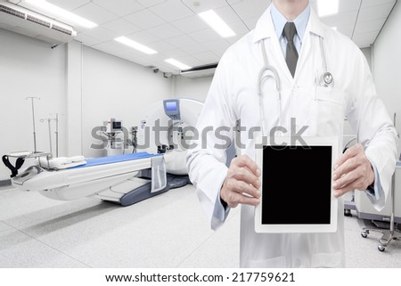 doctor presenting empty digital tablet screen at computed tomography or computed axial tomography scan machine in hospital room