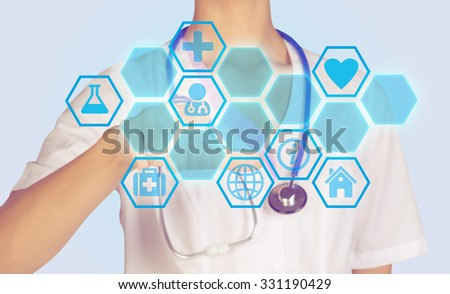 Doctor presses on a digital screen with icons in honecomb. - stock photo