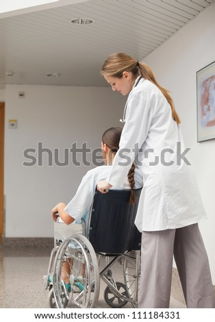 Doctor pushing a wheelchair in hospital ward - stock photo