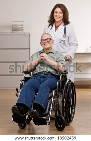 Doctor pushing disabled patient in wheel chair in doctor?s office