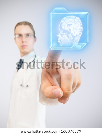Doctor pushing futuristic button and choosing magnetic resonance of human brain. - stock photo