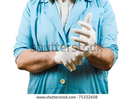 Doctor puts on rubber gloves - stock photo