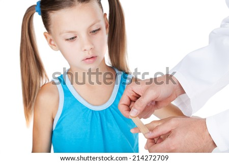 doctor putting plaster on finger isolated on white background. little girl standing with plaster on finger  - stock photo