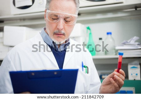 Doctor reading a document while holding a test tube in a laboratory - stock photo