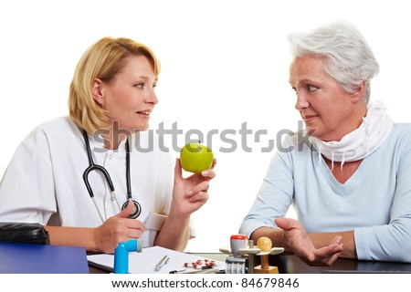 Doctor recommending a green apple to senior woman