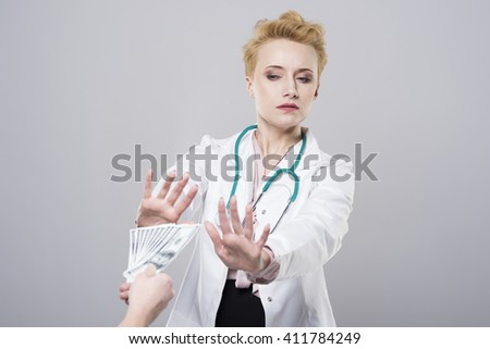 Doctor rejects to take a bribe - stock photo