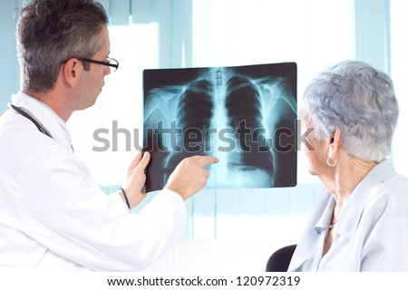 Doctor Reviewing X-rays. Doctor explaining diagnosis to his female senior patient. - stock photo